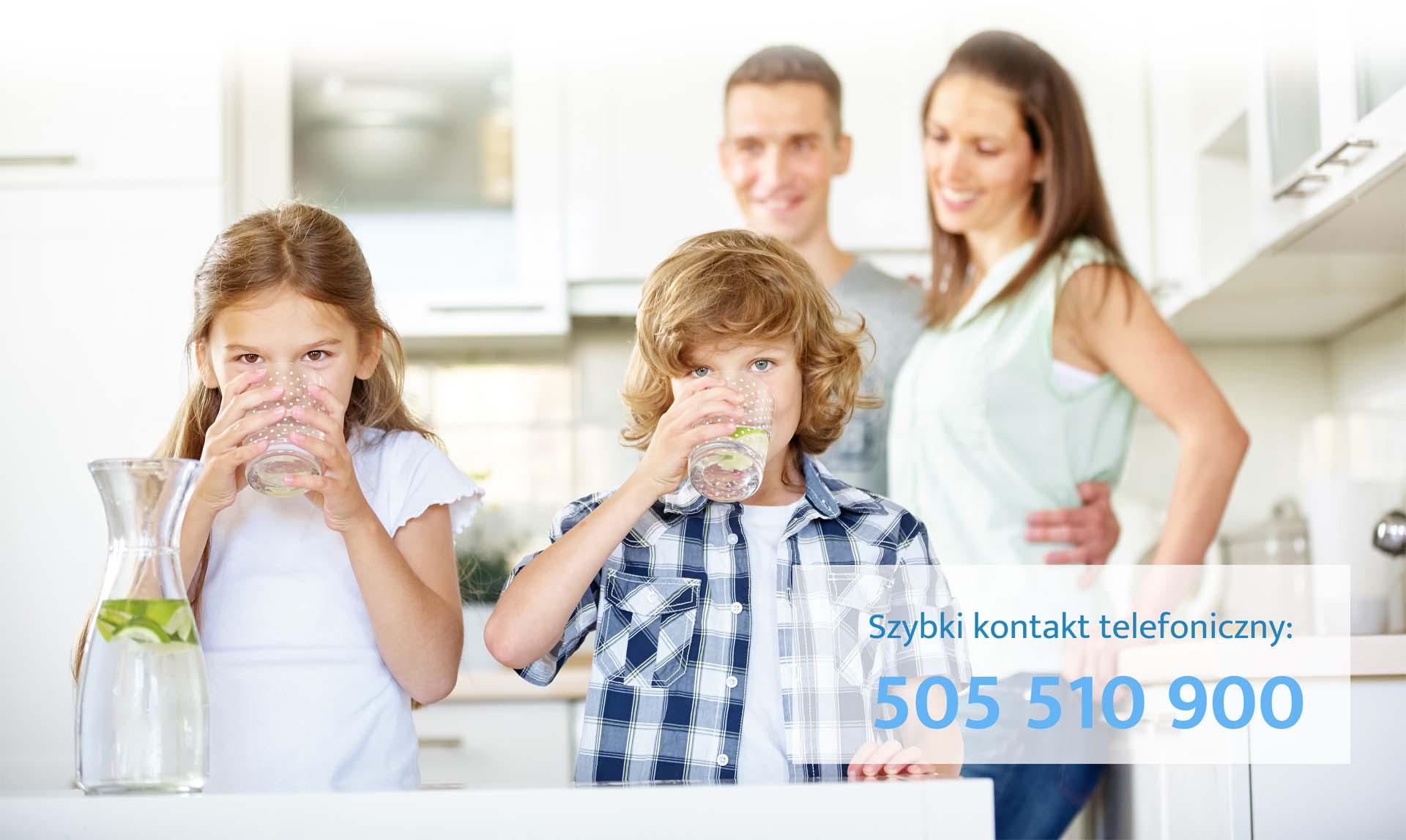 Kinder trinken frisches Wasser mit Limetten in der Küche vor den Eltern